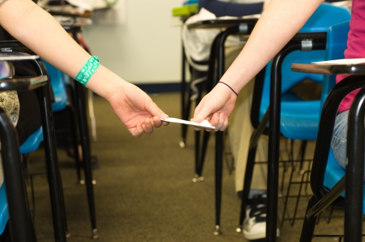 Girls hands passing a note